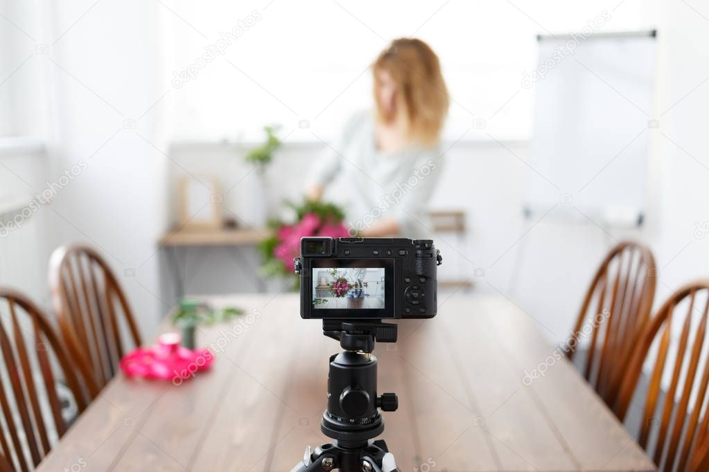 Defocused photo of woman blogger recording on camera master