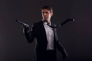Image of mafia man with emerging tie in leather gloves with gun