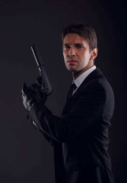 Image of mafia man in leather gloves with gun