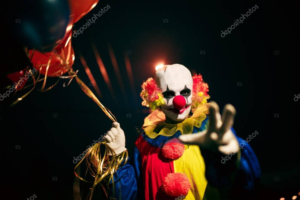 Picture of smiling clown with balls in hands at night