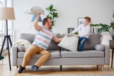 Image of father fighting with son cushions on gray sofa