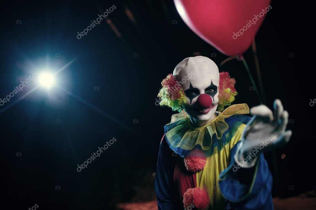 Image of clown with red balloon on background of burning lantern