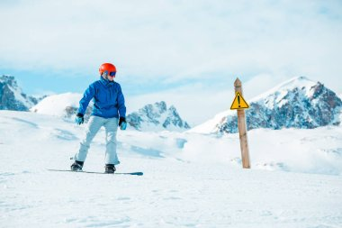 Picture of snowboarder wearing helmet at warning sign on mountain