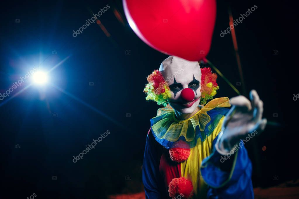 Photo of clown with red balloon on background of burning lantern