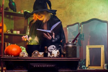 Portrait of witch in black hat reading spell over pot with green steam