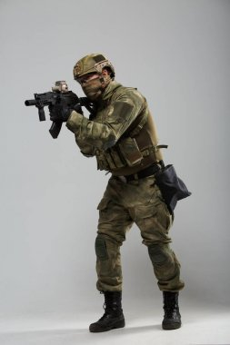 Portrait of full-length military man in camouflage with gun
