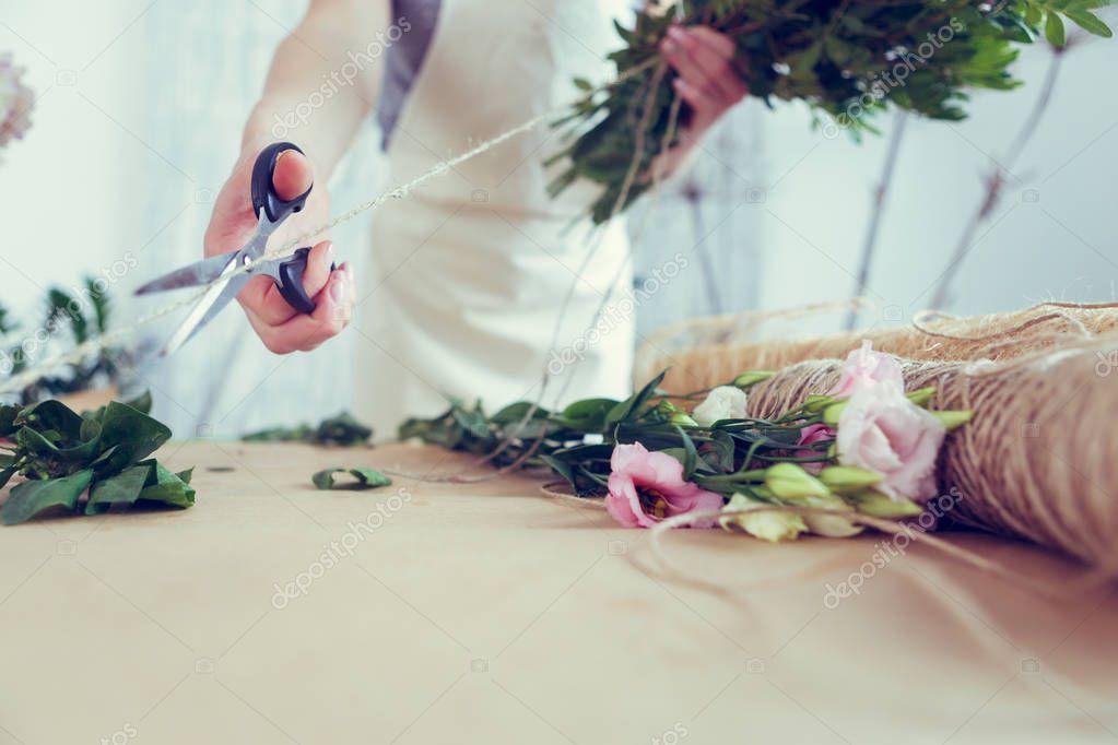 Woman florist makes beautiful bouquet