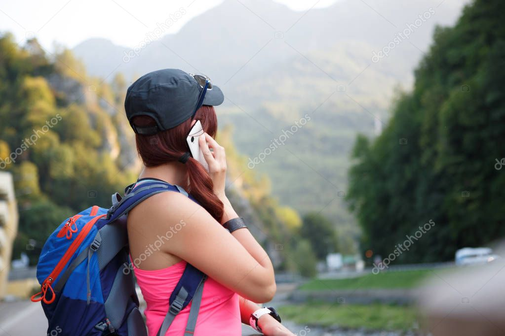 Image from back of tourist girl talking on smartphone
