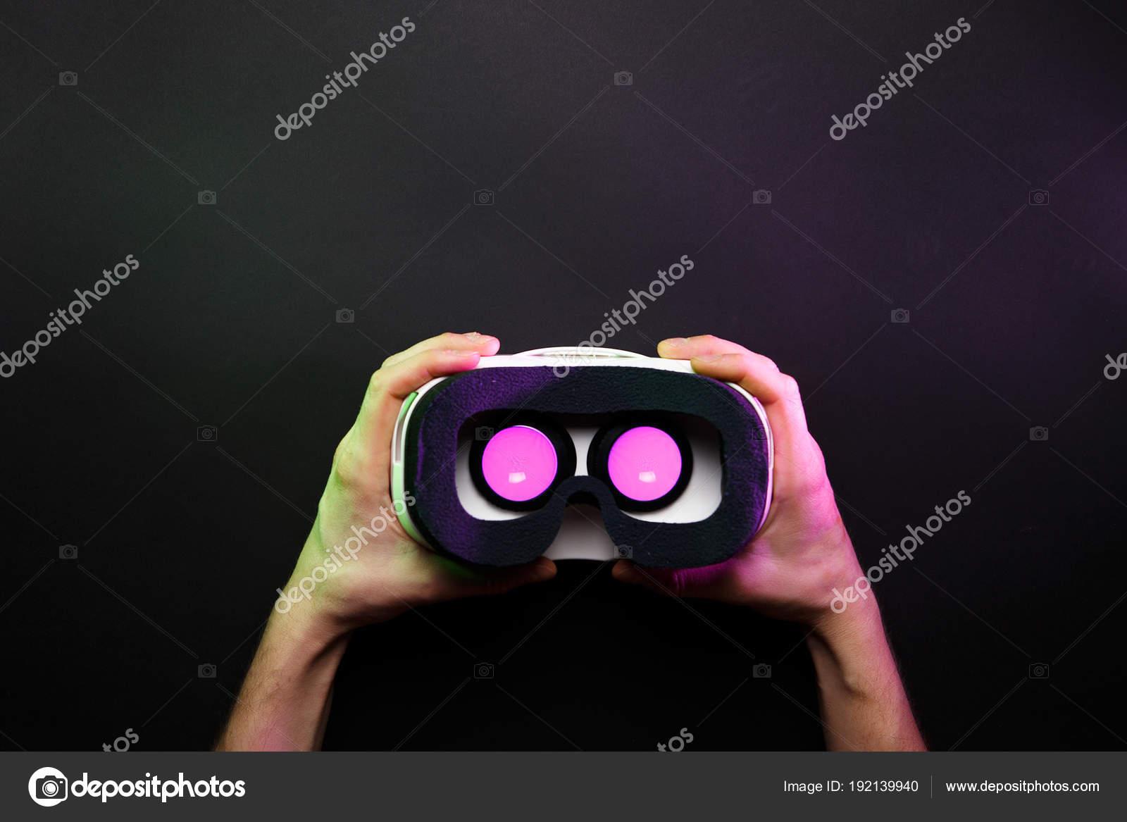 Bril Met Licht : Foto van handen met vr bril met roze licht branden op zwarte