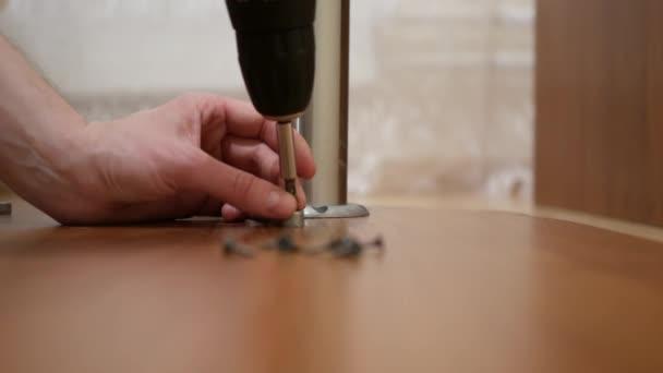 männliche möbel mover möbel heim und bewegliche konzept nahaufnahme von männlichen händen montage beine zu tisch