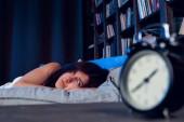 Foto brunetka s nespavostí ležící na posteli vedle Budík v noci
