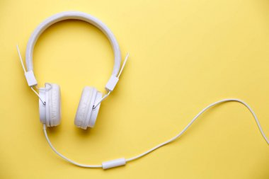 Photo of white headphones for music on yellow background