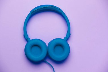 Blue headphones on empty purple background