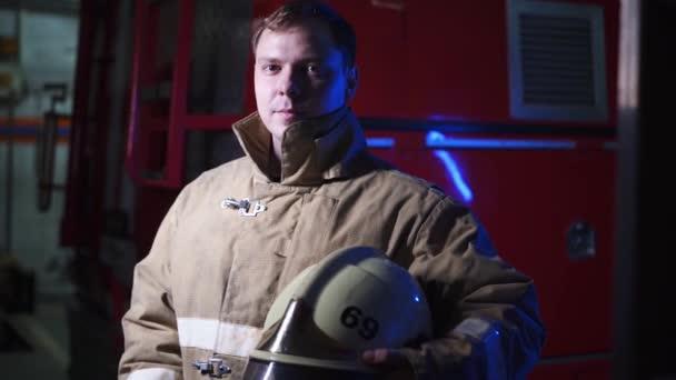 záchranář stojí u červeného hasičského vozu a drží ochrannou helmu