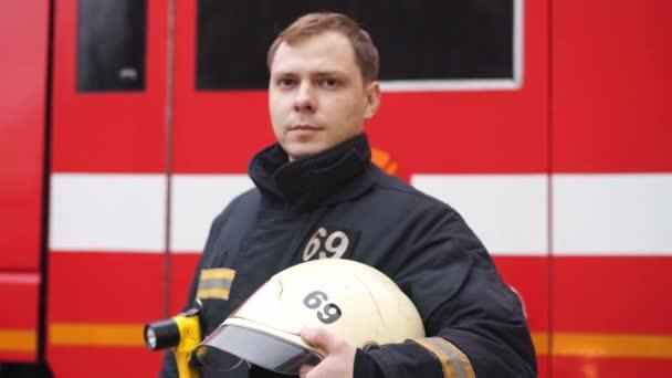 pohledný zachránce v černé uniformě s ochrannou přilbou