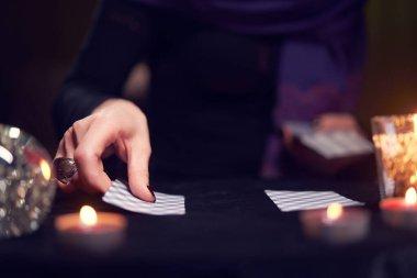 Falcıların eli, masada mumlarla fal bakan kartlarla yakın çekim.