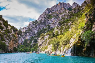 catamarans and kayaks with tourists sailing on river