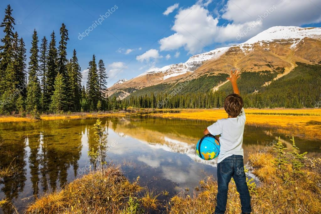 boy standing on shore of lake