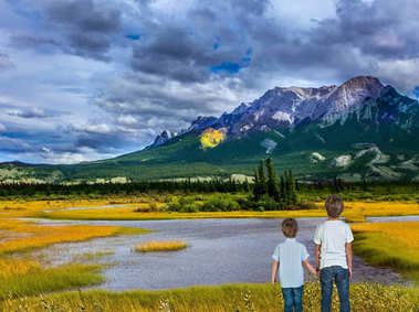Two lovely boys admire the beauty of mountains and lakes. Magnificent landscape in the Rocky Mountains. The concept of ecological and active tourism