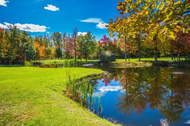 Very nice park. Golf Club on the road to Bromont, French Canada. Concept of Golf tourism. Red and green autumn foliage is reflected to clear water of the lake