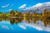 Fotografie Der See, rot-Orange Bäume und Berge... Heller, leuchtender Tag in den kanadischen Rockies. Canmore, in der Nähe von Banff. Konzept des Wanderns