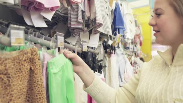 a65cb3624 Young happy pregnant woman choosing newborn clothes at baby shop ...