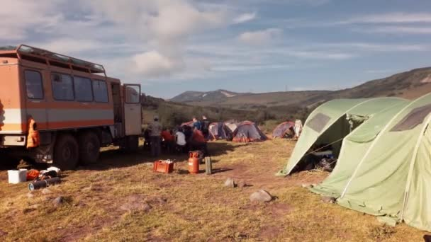 Group of tourists dismantles tent camp, loads things in an off-road Kamaz car and leaves from a resting place. Timelapse stock footage video