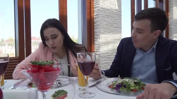 Milující pár v restauraci má večeře, chlap je krmení dívku salát zpomalené stopáže videa