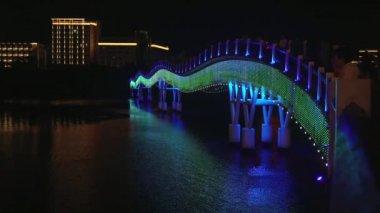 Night illumination of the New pedestrian bridge Rainbow across the Sanya River time lapse stock footage video