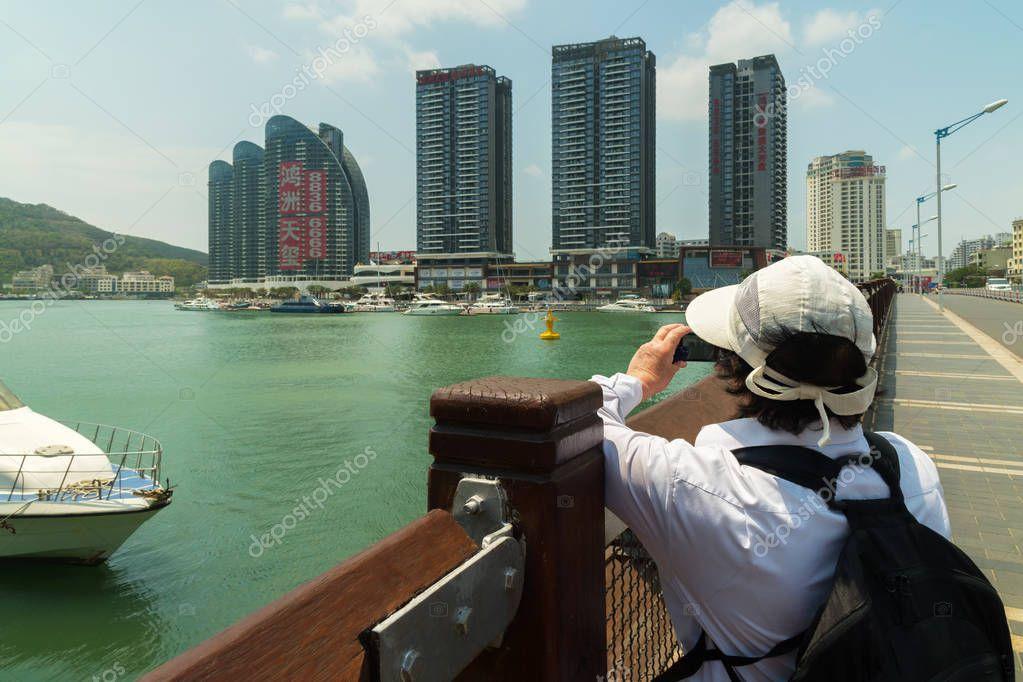 Tourist photographs modern skyscrapers on the embankment of the Sanya River in Sanya City on Hainan Island