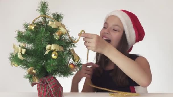 Beautiful naughty teenager girl trying to dress up a New Year tree, but the Christmas tree always falls, violent emotions on white background stock footage video