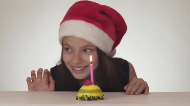 Beautiful naughty girl teenager in Santa Claus hat secretly blows out candle on festive cake and happily hides on white background stock footage video