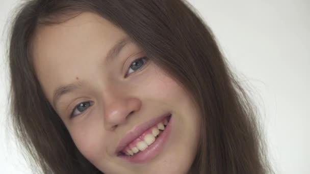 Szép boldog tinédzser lány mosolyogva és nevetve közelről a fehér háttér stock footage videó