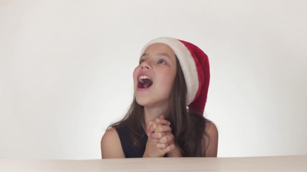 Beautiful happy girl teenager in a Santa Claus hat emotionally expresses a joyful surprise on white background stock footage video.