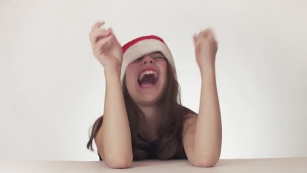 Beautiful unhappy girl teenager in a Santa Claus hat emotionally desperately crying and violently expressing protest on white background stock footage video.