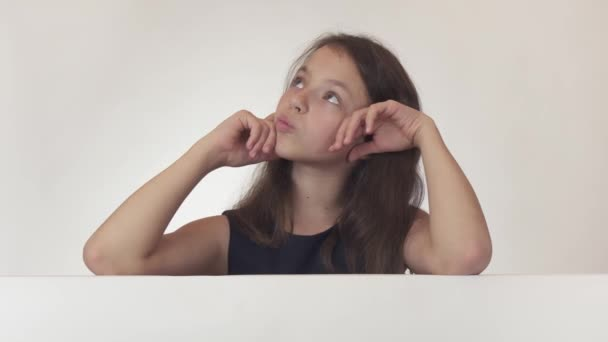 Beautiful girl teenager reflects, looks at the poster with the information, finds there what she wanted and is thrilled on white background stock footage video.
