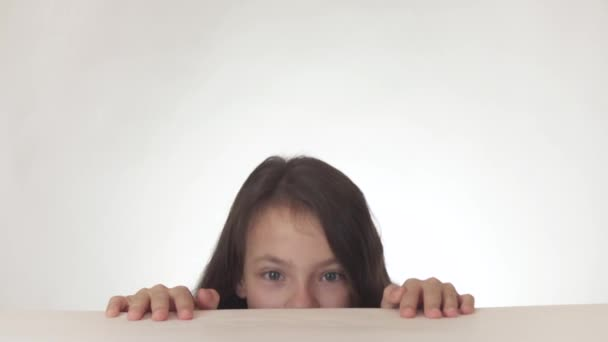 Beautiful happy naughty teen girl having fun getting out from under the table and hiding back on white background stock footage video.