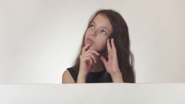Beautiful girl teenager reflects, looks at the poster with the information, finds there what she wanted and rejoices on white background stock footage video.