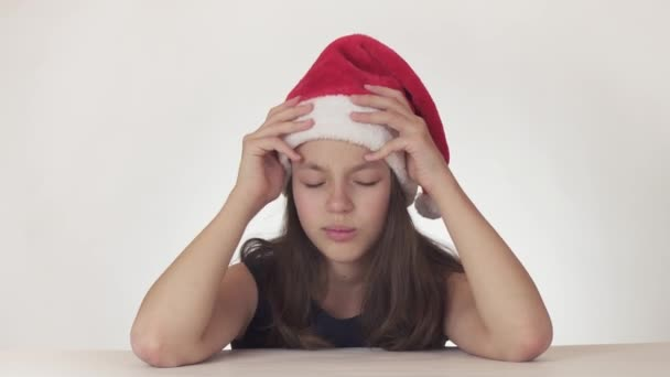 Beautiful unhappy girl teenager in a Santa Claus hat emotionally expresses despair and begins to cry on white background stock footage video.