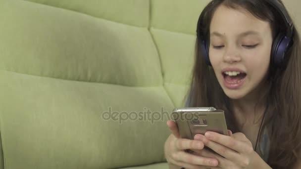 Beautiful teen girl in headphones singing karaoke songs in smartphone stock footage video