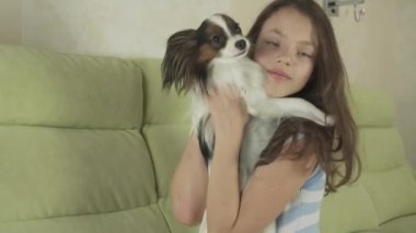 Beautiful happy teenage girl having fun playing with her dog Papillon Continental Toy Spaniel stock footage video