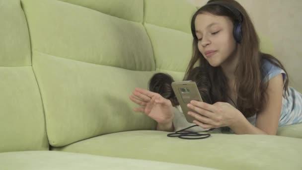 Beautiful teen girl in headphones singing karaoke songs in smartphone with dog stock footage video