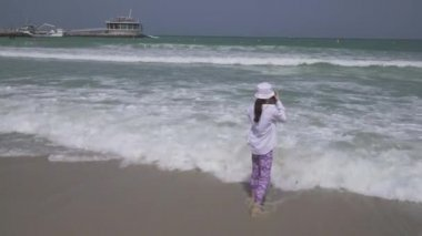 Teenage girl takes pictures of the sea waves of the Persian Gulf on smartphone on the beach of Dubai stock footage video