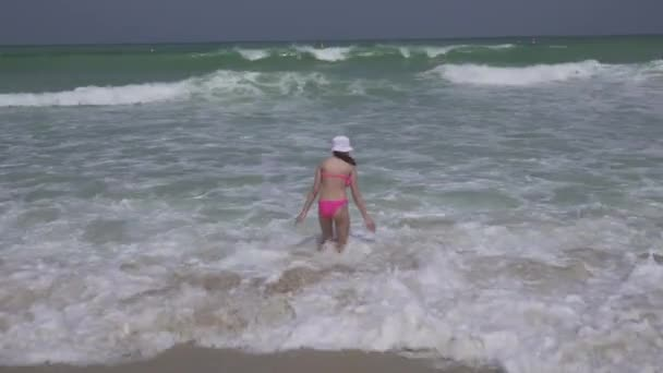 Teenage girl in a bathing suit happily jumps in the waves of Persian Gulf on beach of Dubai stock footage video