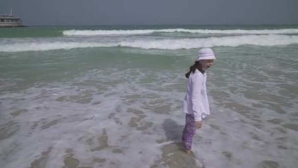 Teenage girl in clothes joyfully jumping in the waves of Persian Gulf on the beach of Dubai stock footage video