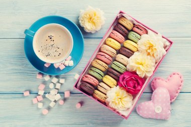 Macaroons, coffee and marshmallow on wooden table