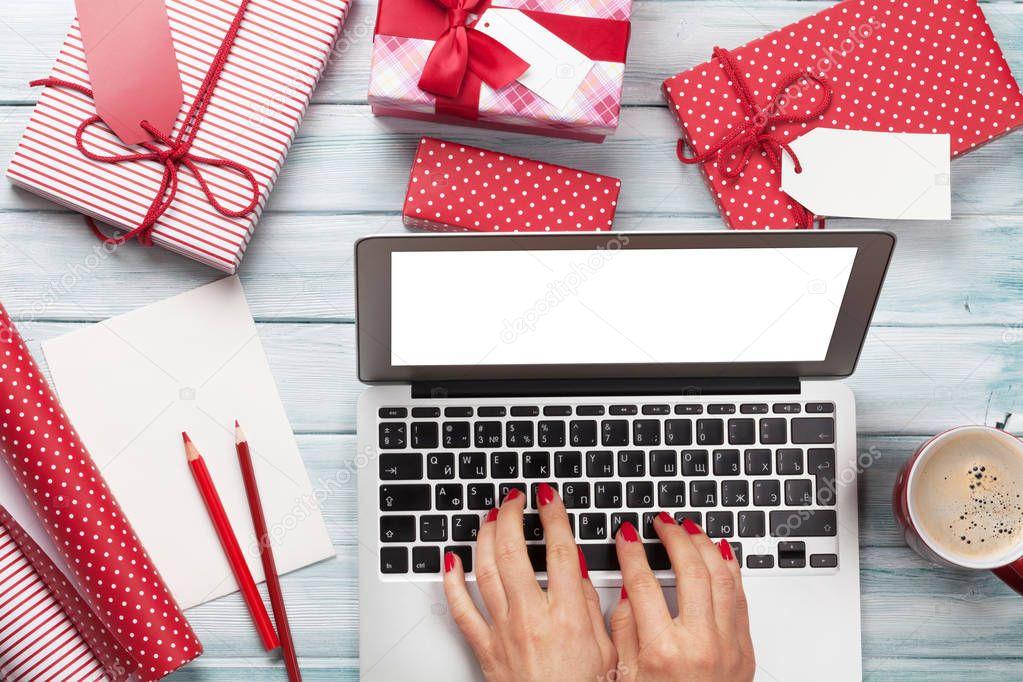 Weibliche Arbeit am Laptop und Geschenke Verpacken — Stockfoto ...