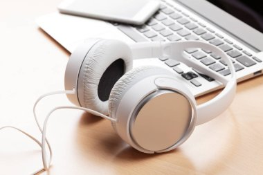 Headphones over laptop on table