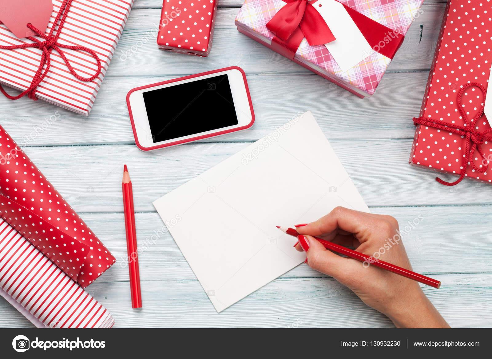 Weibliche schreiben Grußkarte und Weihnachtsgeschenke verpacken ...