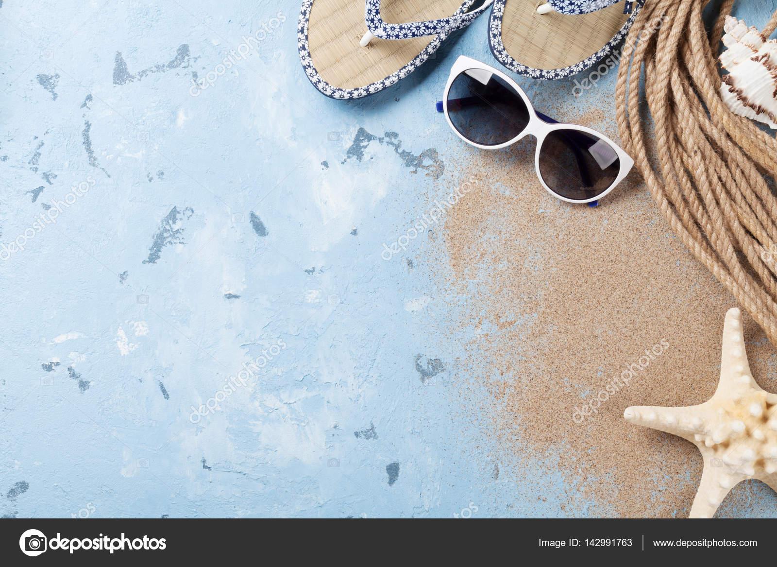 9150d4ad1d54e Plaj aksesuarları, güneş gözlüğü, parmak arası terlik ve deniz kabukları  üzerinde taş arka plan, üstten görünüm — karandaev - Fotoğraf